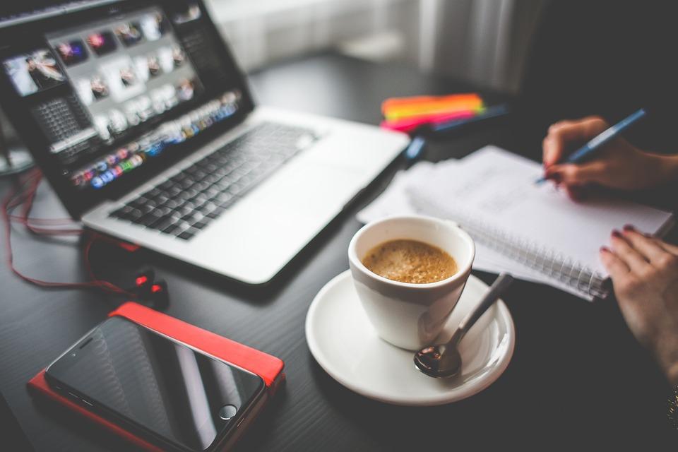 パソコンとコーヒーと共にメモをする女性