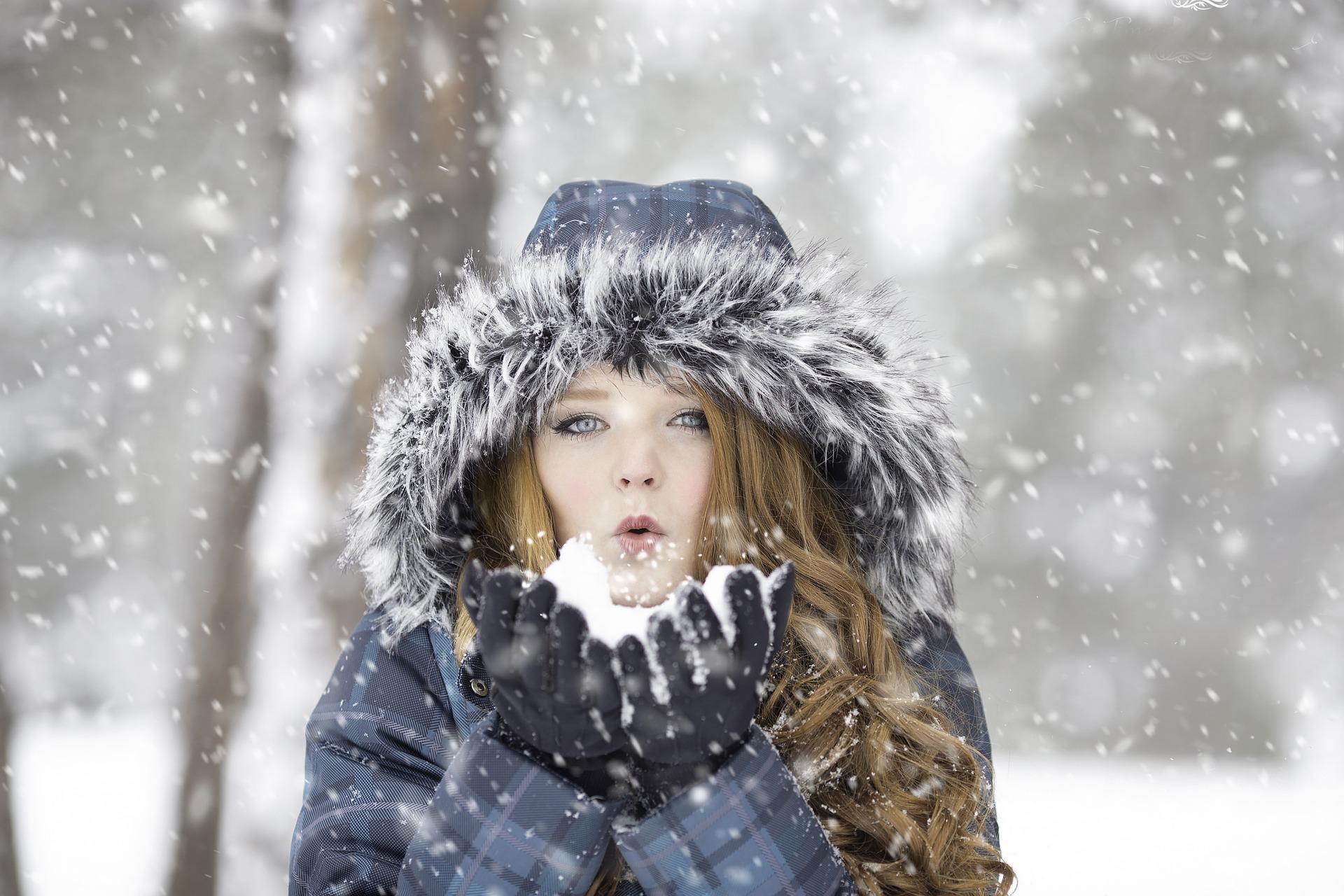 雪で遊ぶコートを着た女性