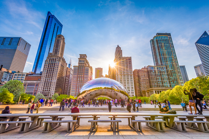 CHICAGO - ILLINOIS: MAY 9, 2018: Tourists visit Cloud Gate in Millennium Park in the late afternoon.